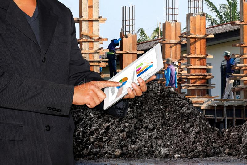Business Construction Site, Businessman using tablet and Blurred background Construction workers royalty free stock photo
