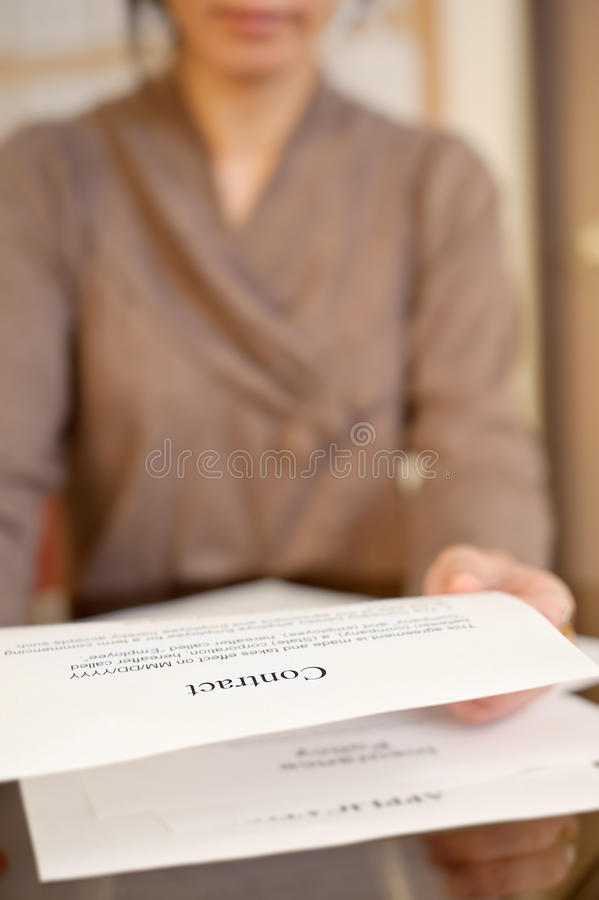 Business contract. Woman reading business contract paper in office stock photos