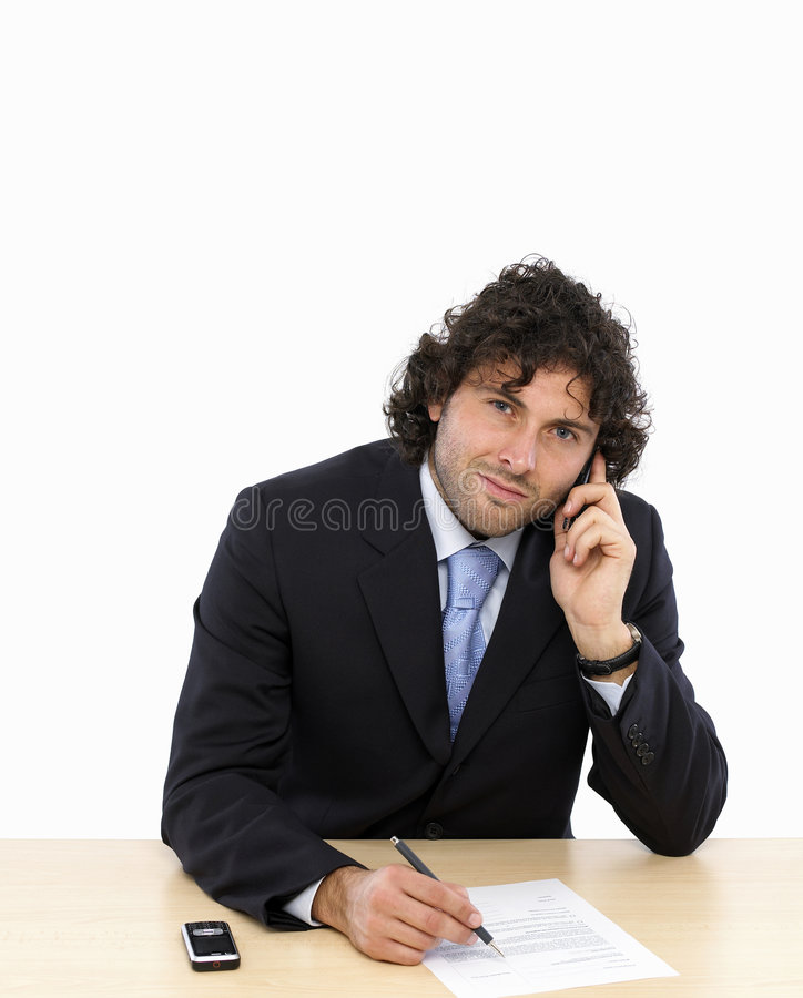 Business contract. Young businessman is writing a contract talking on mobilphone stock photography