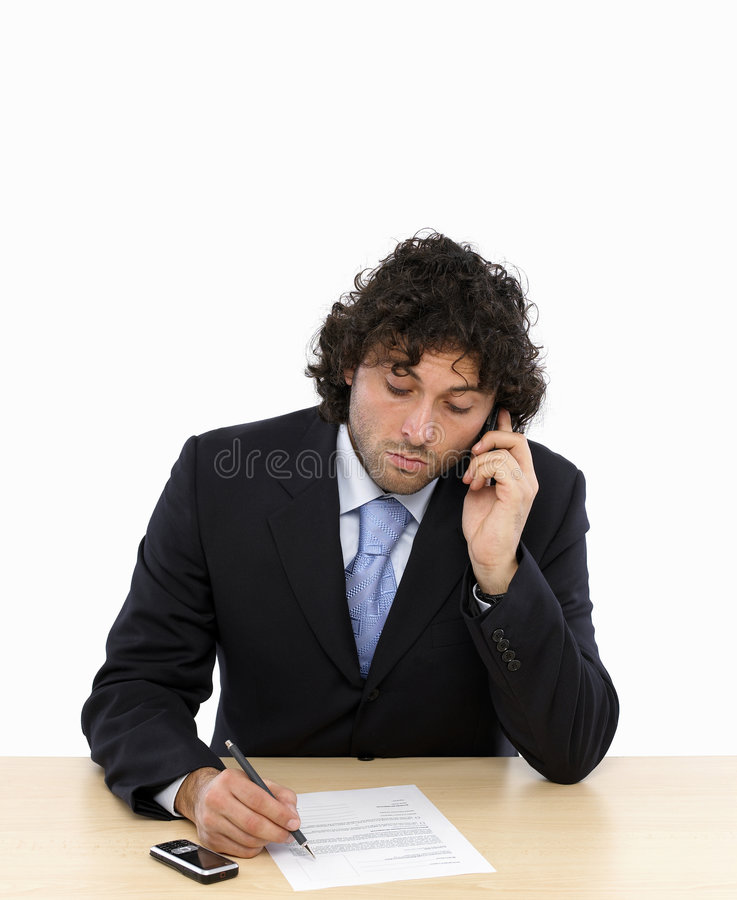 Business contract. Young businessman is writing a contract talking on mobilphone stock photos