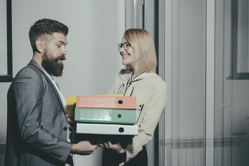 Business cooperation and teamwork. Man help woman to carry binders in office. Businesswoman and businessman with folders. Business cooperation and teamwork. Man royalty free stock photos