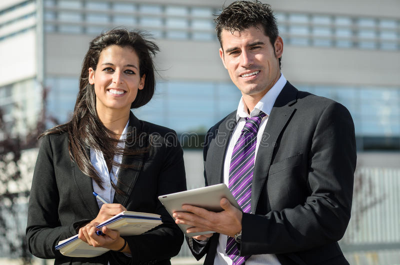 Business couple. Business men and women smiling and taking notes in tablet and notebook outdoors stock photography