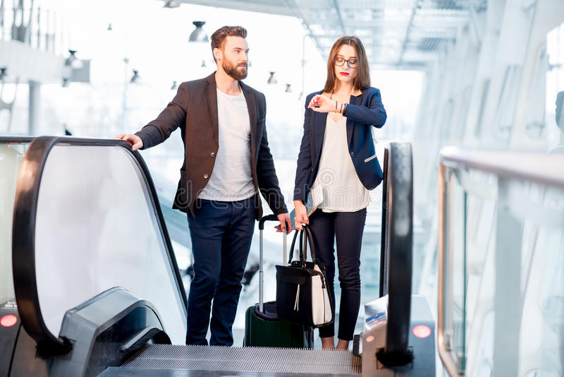 Business couple at the airpot. Business couple with baggage checking time getting up on the escalator at the airport stock photos