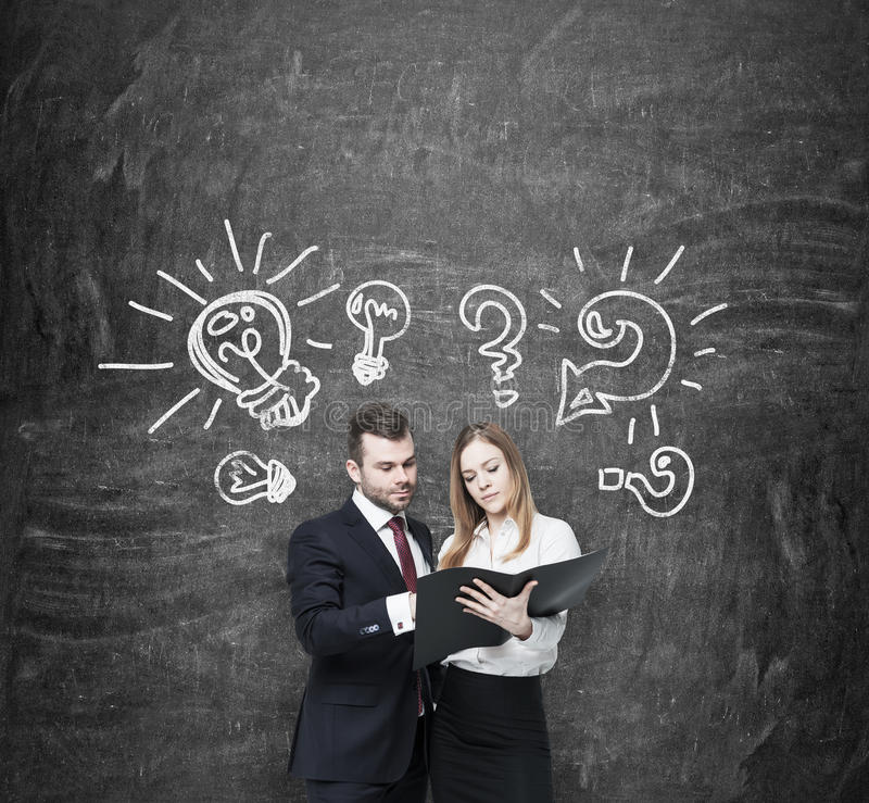 Business couple are arguing about business project . A couple in formal clothes are holding a black document folder. Light bulbs. And question marks are drawn stock photography