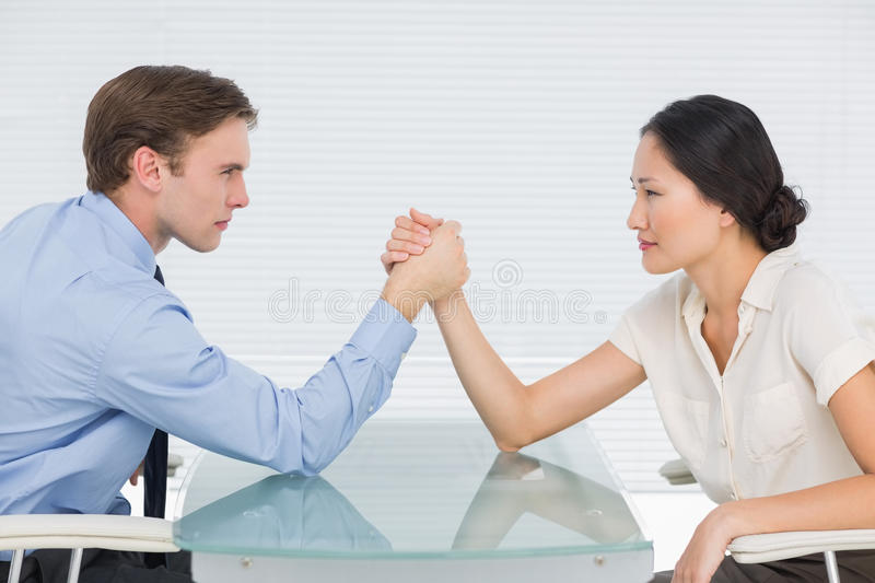 Business couple arm wrestling at desk. Side view of serious young business couple arm wrestling at office desk royalty free stock photo