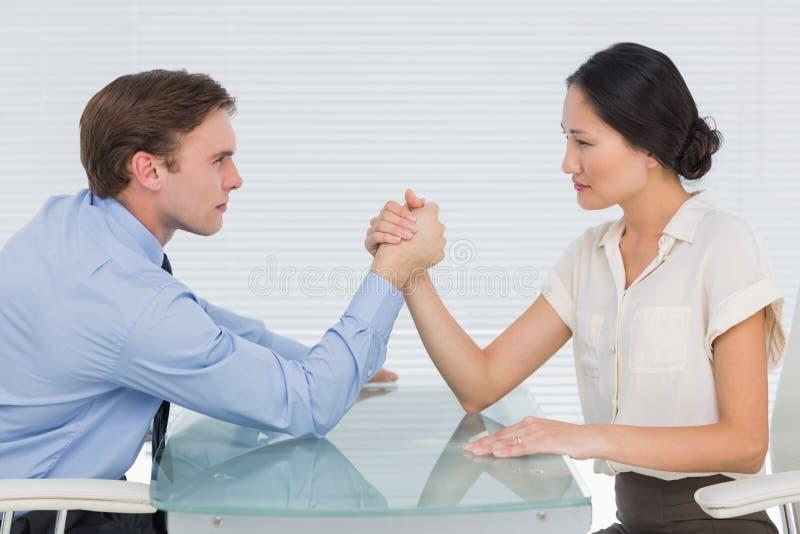 Business couple arm wrestling at desk. Side view of serious young business couple arm wrestling at office desk royalty free stock images