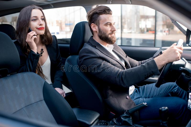 Business couple in the car. Businesswoman on the backseat with elegant men driving a car in the city. Worried about a delay to an important meeting royalty free stock photo