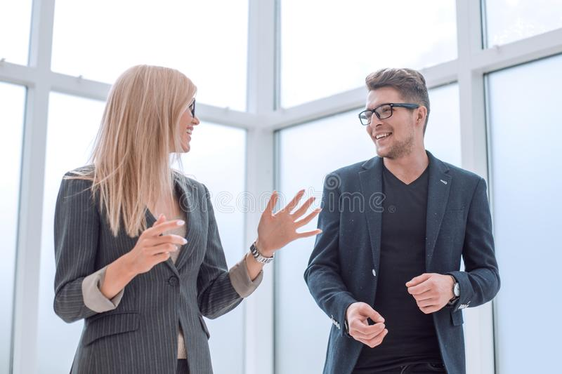 Business couple discussing something standing in the office stock image