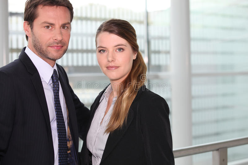 Business couple in front of window stock photography