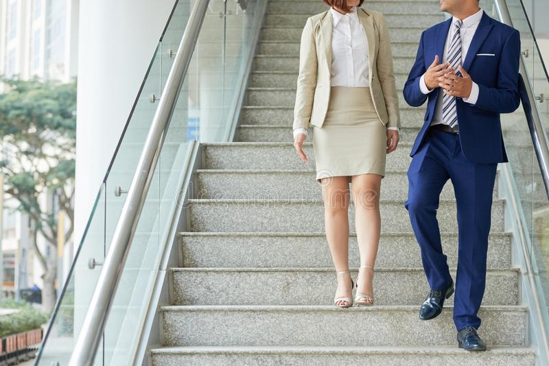 Business couple getting down the stairs stock images