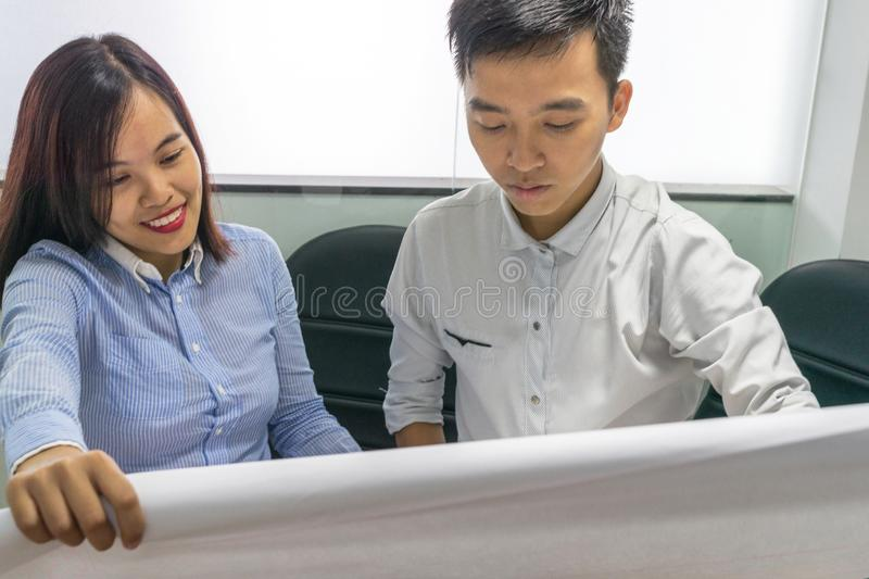 Business couple holding a blueprint and having discussion at workplace stock photos