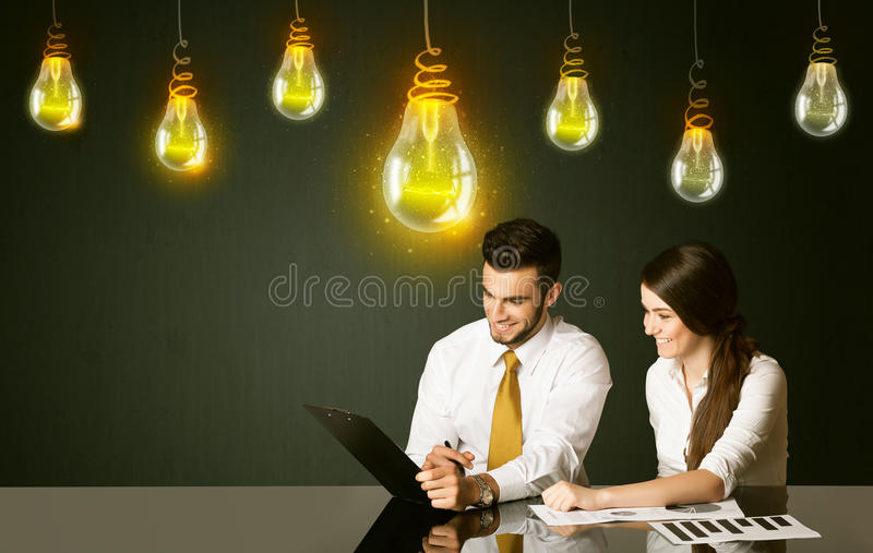 Business couple with idea bulbs. Business couple sitting at the black table with idea bulbs on the background stock image