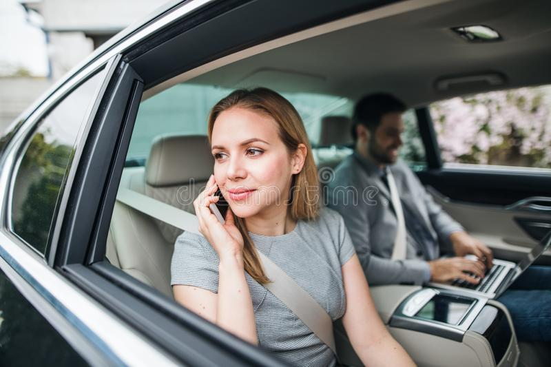Business couple with laptop sitting on back seats in car, working. Young business couple with laptop and smartphone sitting on back seats in car, working royalty free stock photos