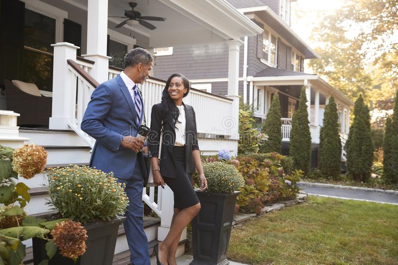 Business Couple Leaving Suburban House For Commute To Work royalty free stock images