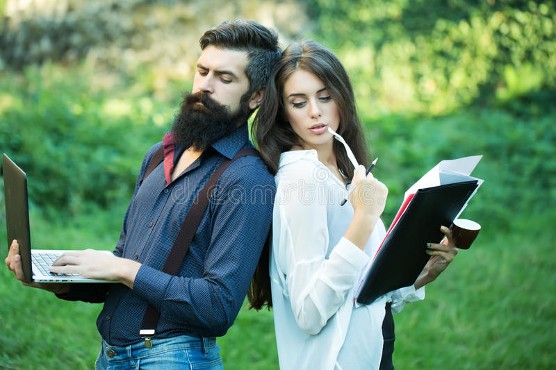 Business couple in park. Business young pair of slim women and men with long lush black beard with office devices of laptop glasses mobile phone paper folder and stock images