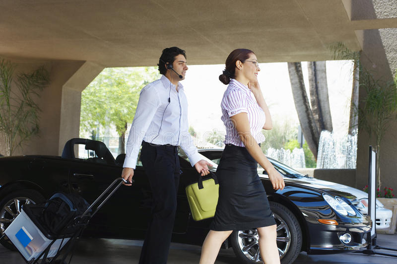 Business Couple Passing By Car. Side view of business couple passing by car stock photography