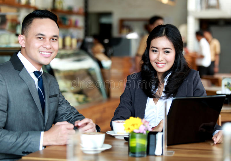 Business couple smiling and looking at camera while meeting royalty free stock images