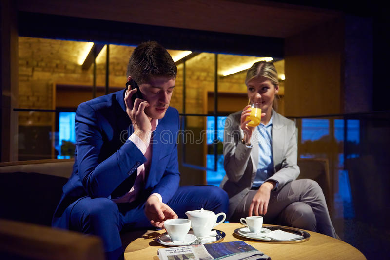 Business couple take drink after work. Young business people couple relaxing after work in bar restaurant and take drink stock photography