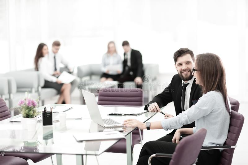 Business couple talking while sitting at a Desk in a modern office stock images