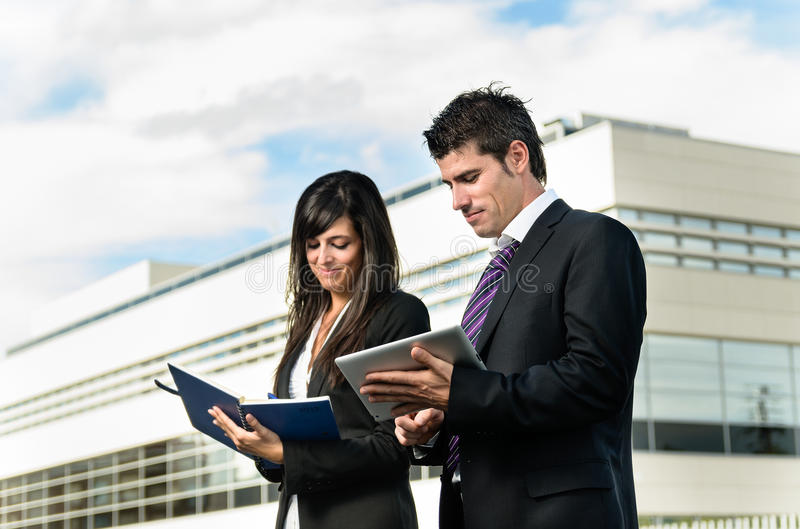 Business couple working. Cheerful business people taking notes in front of company building stock photo