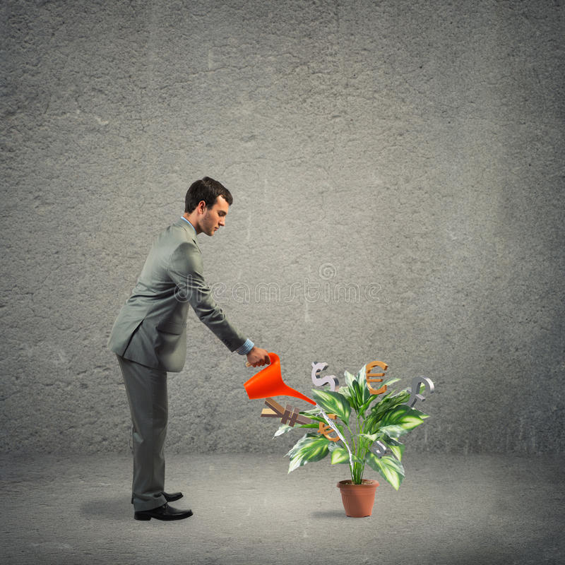 Business creation. Image of a businessman with a watering can stock photo