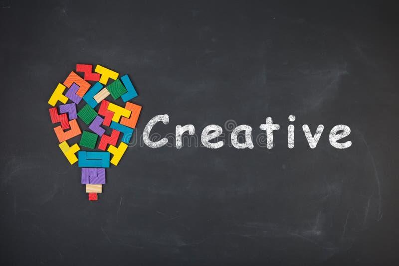 Business creative idea concept - inscription and jigsaw blocks on the blackboard. Business creative idea concept - inscription and bulb of jigsaw blocks on the royalty free stock photos