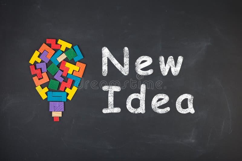 Business creative idea concept - inscription and jigsaw blocks on the blackboard. Business creative idea concept - inscription and bulb of jigsaw blocks on the stock image
