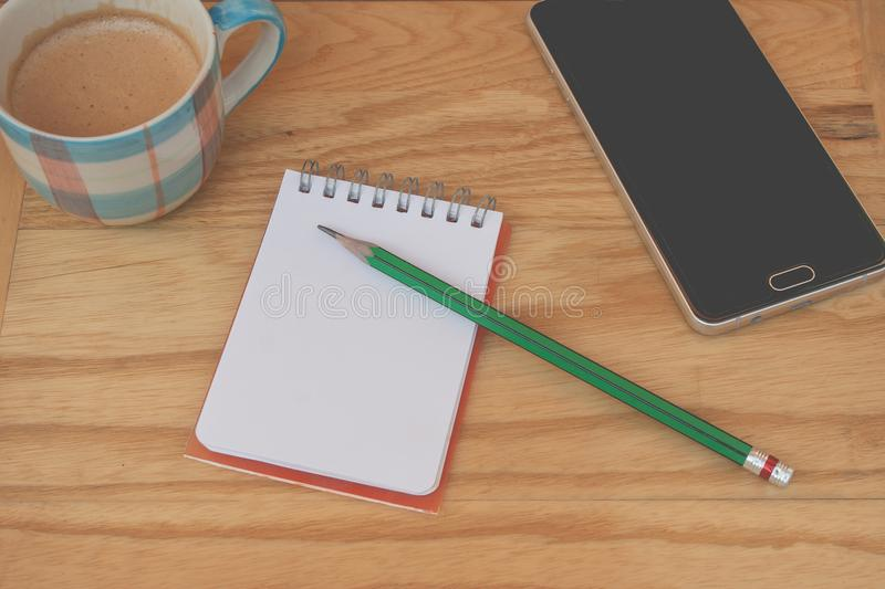 Business creative and idea concept: used green pencil put on notebook with smartphone and coffee cup put on wooden table. stock images