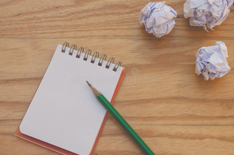 Business Creative and Idea Concept : Used green pencil put on notebook with white crumpled paper ball put on wooden table. stock photo