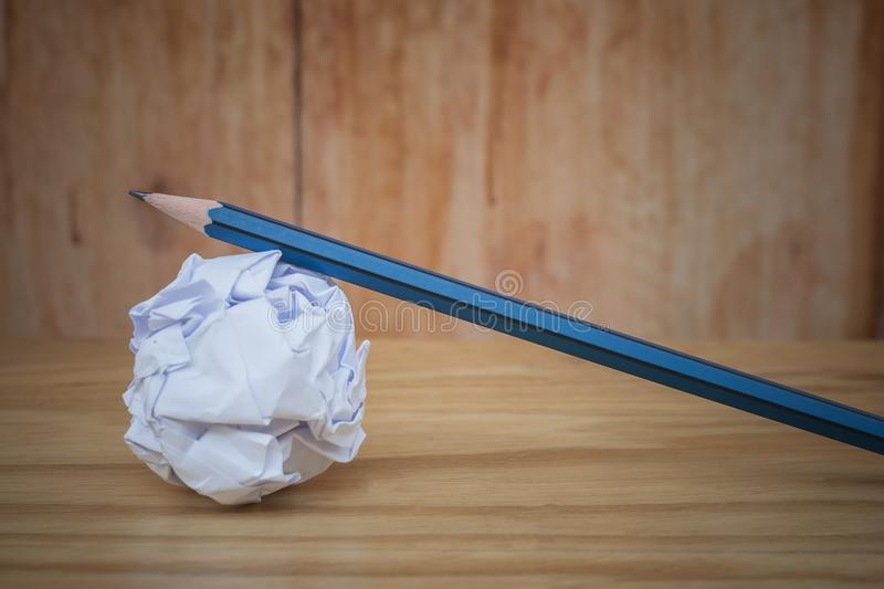 Business creative and idea concept: used pencil with white crumpled paper ball put on wooden floor. stock images