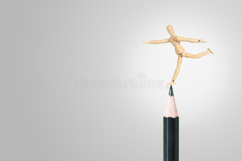 Wooden figure mannequin standing on used black pencil. stock photos