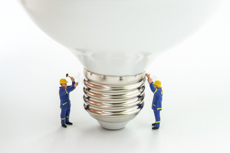Business creative idea, power or energy generator concept, miniature people figurine engineer worker help building light bulb on. White background stock image