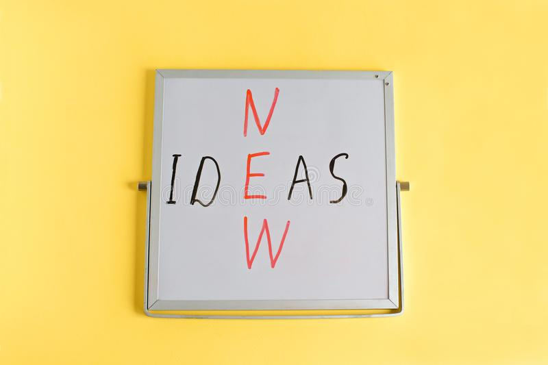 Business creative New ideas concept words written on mini chalkboard on yellow background. Ideas words. royalty free stock images