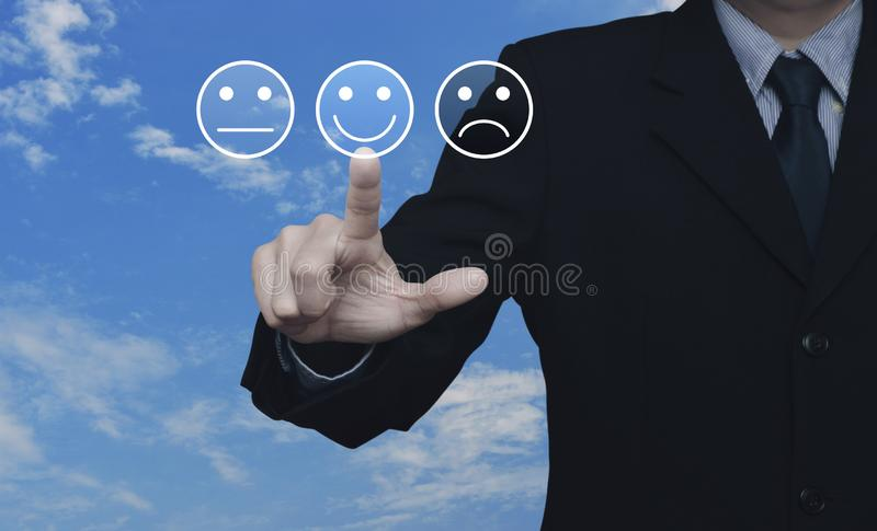 Business customer service evaluation and feedback rating concept. Businessman pressing excellent smiley face rating icon over blue sky with white clouds stock images