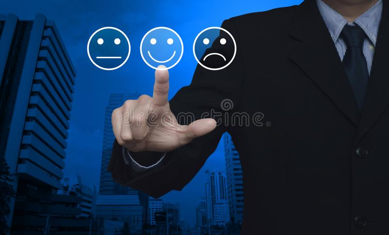 Business customer service evaluation and feedback rating concept. Businessman pressing excellent smiley face rating icon over modern office city tower, Business stock photography