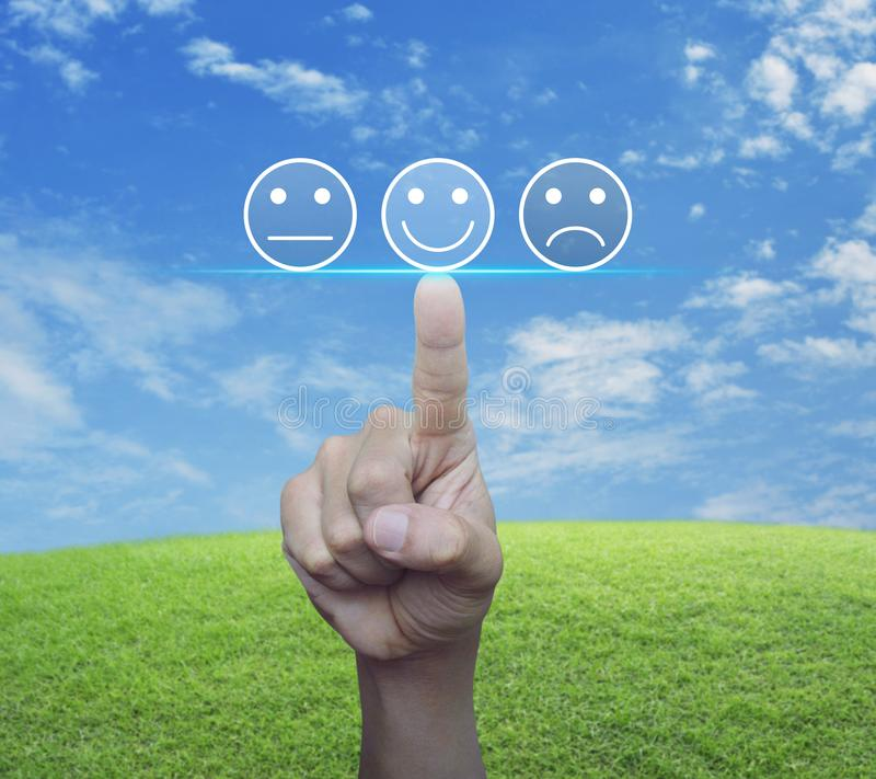 Business customer service evaluation and feedback rating concept. Hand pressing excellent smiley face rating icon over green grass field with blue sky, Business stock image