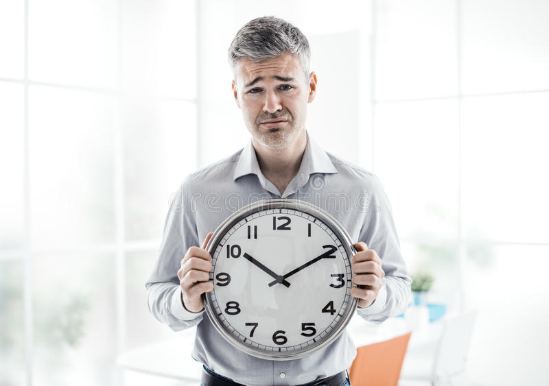 Business and deadlines. Business, time management and deadlines: sad businessman holding a clock, he is missing a deadline stock photo