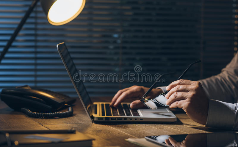 Business and deadlines. Corporate businessman working at office desk with his laptop late at night: working overtime and deadlines concept royalty free stock image