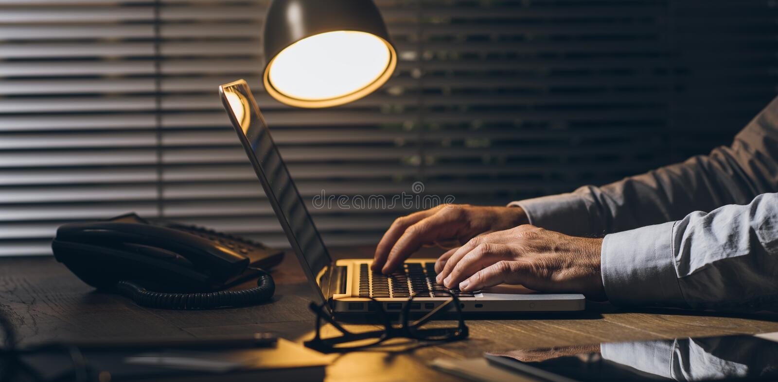 Business and deadlines. Corporate businessman working at office desk with his laptop late at night: working overtime and deadlines concept stock photos