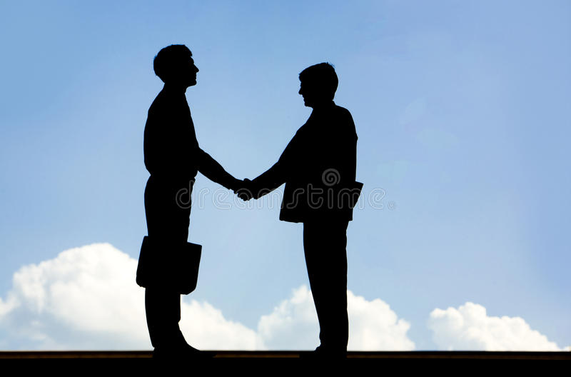 Business deal. Image of silhouette business partners handshaking on a sky background stock image