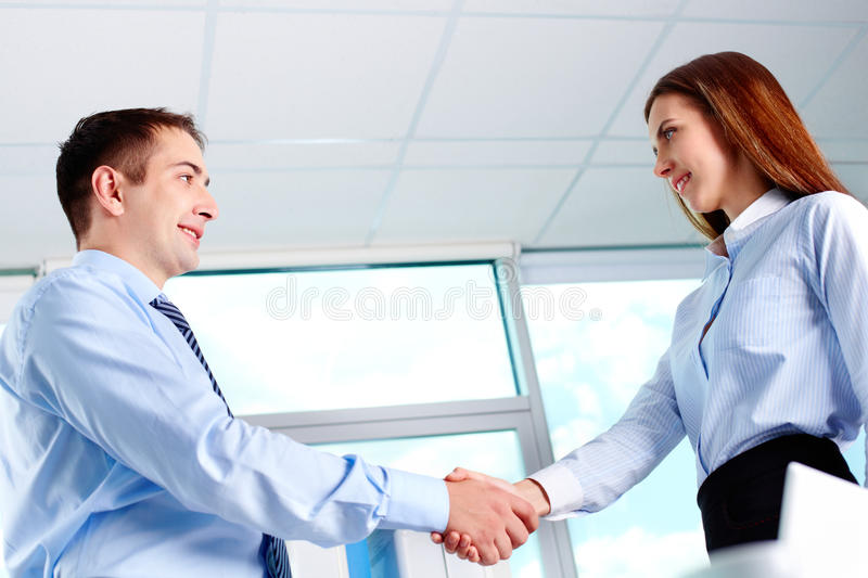 Business deal. Photo of business partners handshaking after striking deal royalty free stock image