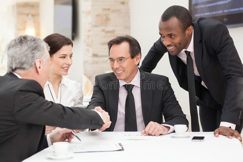 Business deal. Business colleagues sitting at a table during a meeting with two male executives shaking hands stock photography