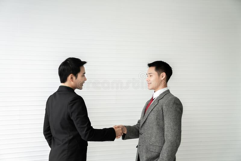 Business deal / two businessman handshake on white background / business concept /asian model.  royalty free stock image