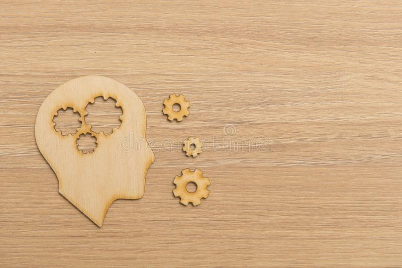 Business and design concept - wooden man head silhouette with gear icon on wooden background royalty free stock image
