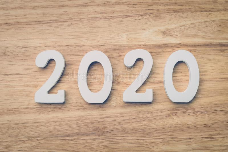 Business and design concept - wooden number 2020 for Happy new year text on wood table royalty free stock photos