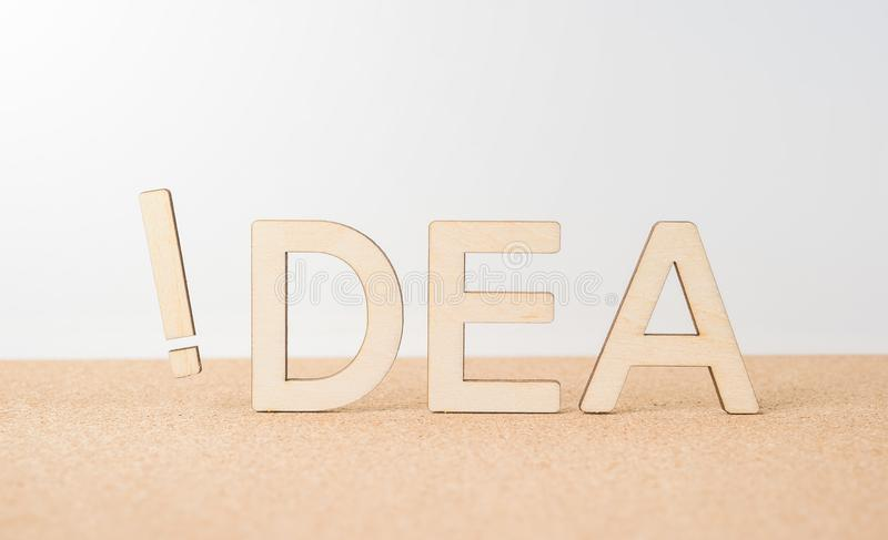 Wooden word ` idea ` with exclamation mark on wooden desktop and white background royalty free stock images