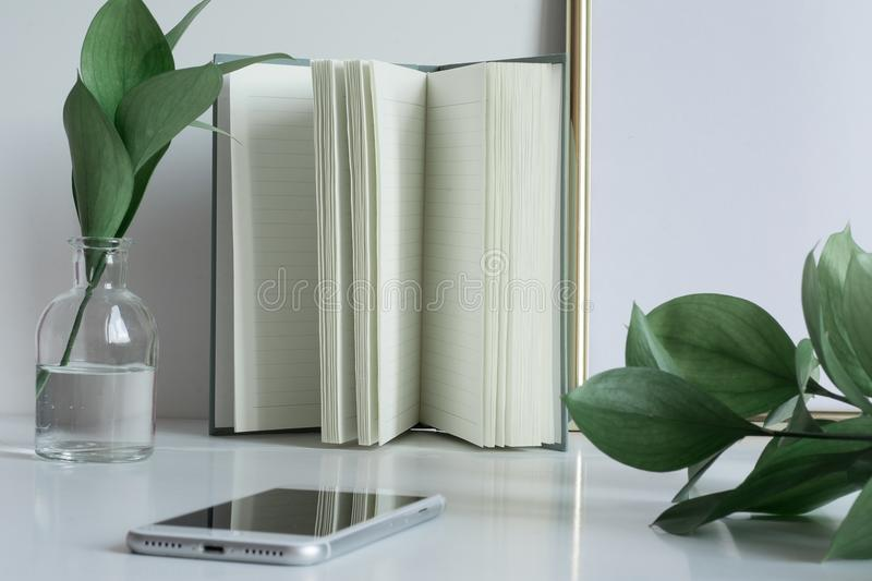 Business desktop with notebook pages vase phone stock photo