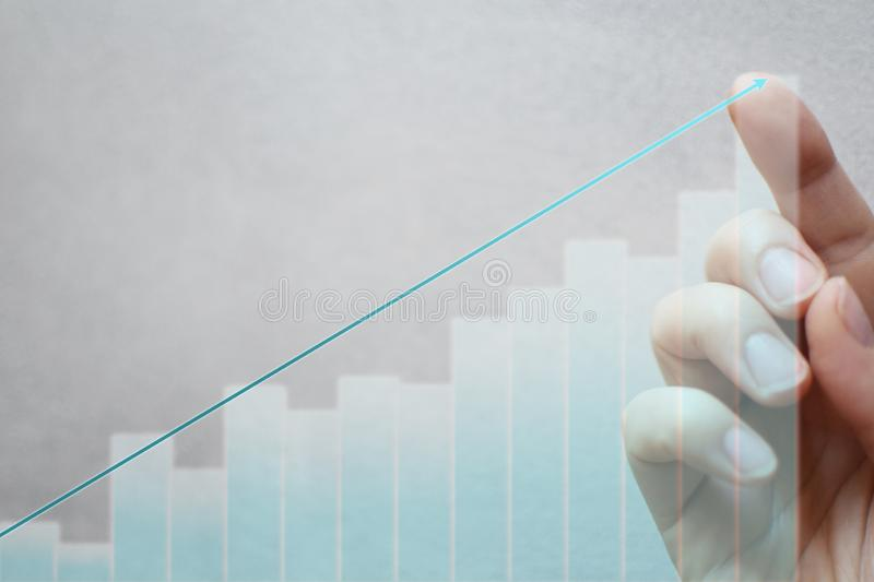 Finger touching arrow on growing graph stock photos
