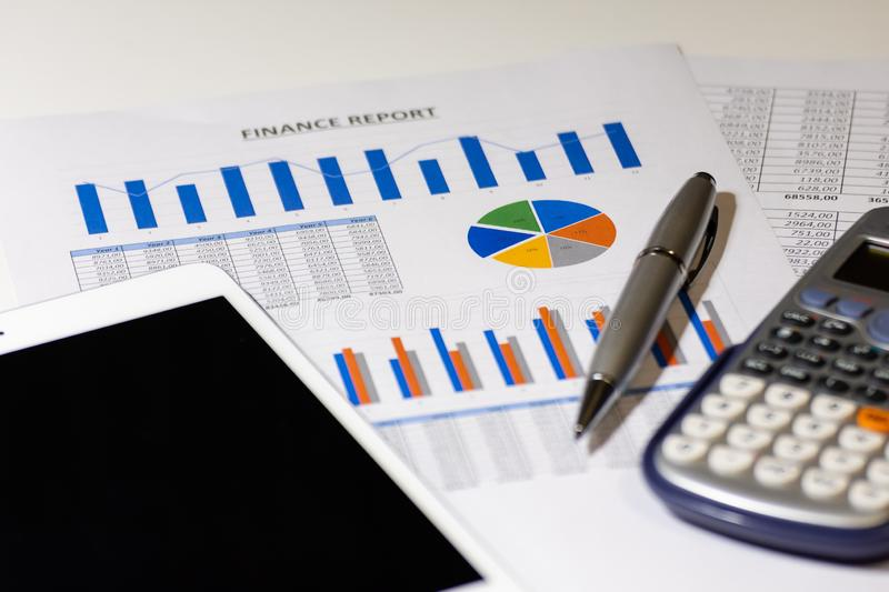 Business diagram on financial report with tablet, pen and calculator stock photo