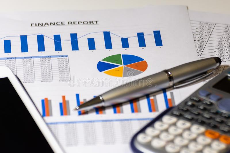 Business diagram on financial report with tablet, pen and calculator stock images